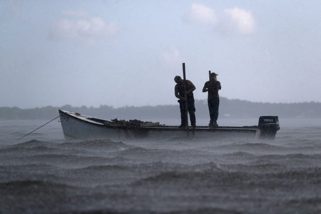 Two oystermen work through a passing rainstorm on their boat in the Apalachicola Bay on Thursday, June 28, 2018.