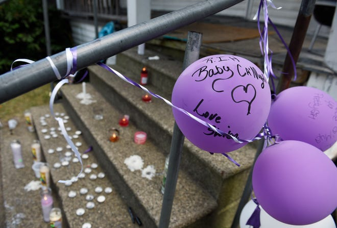 Balloons are tied to the porch railing beside a makeshift memorial site for 1-year-old Ca'mya Davis, who died after falling through a hole in her floor to a water-filled basement.