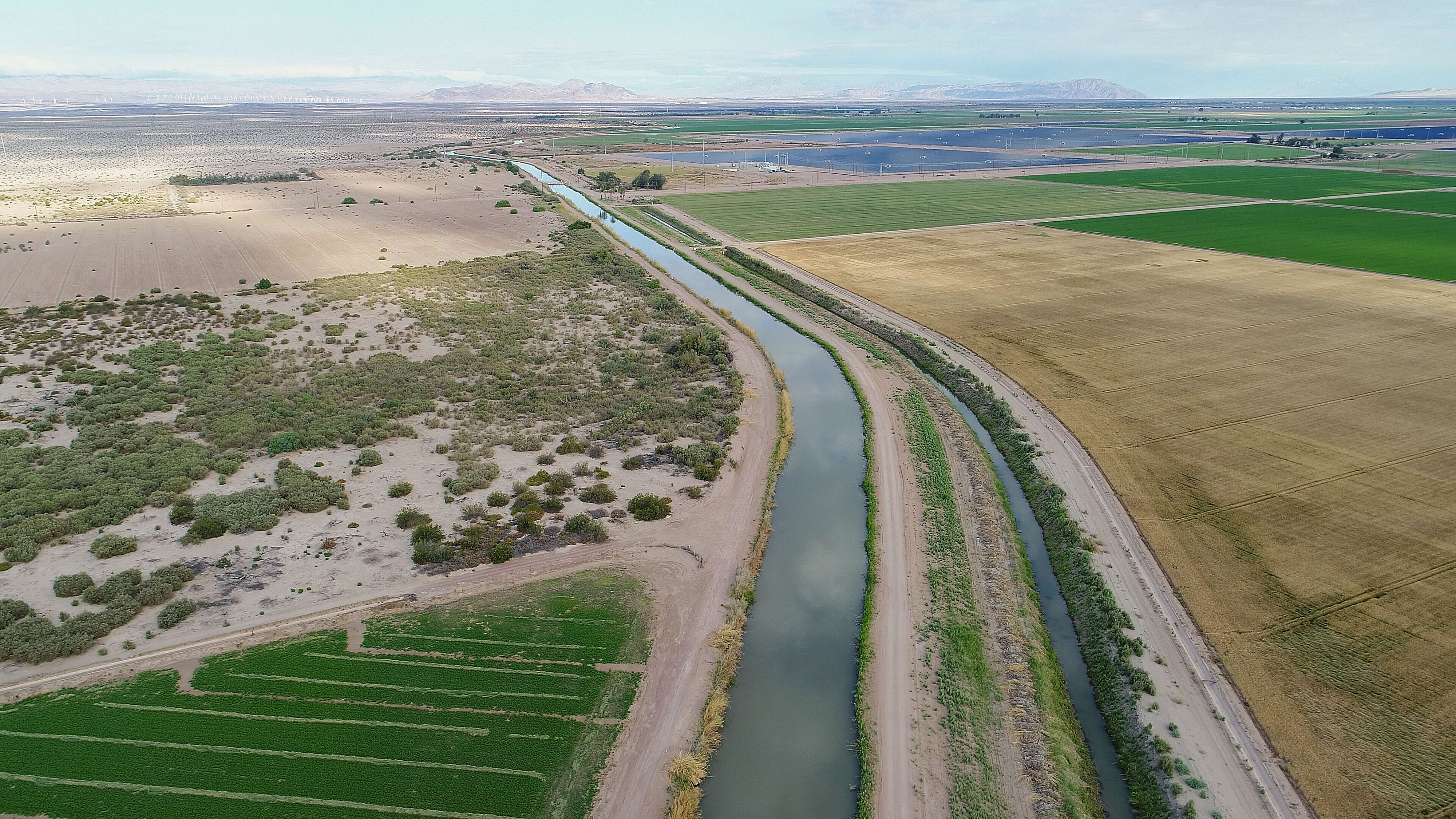 The Westside Main Canal flows past farmland owned by Mike Abatti, as seen from a drone. The Campo Verde solar project can be seen in the background.