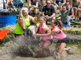 Teams of four people compete to get a pig on a barrel in a muddy water filled pen at the Eldorado Community Picnic.