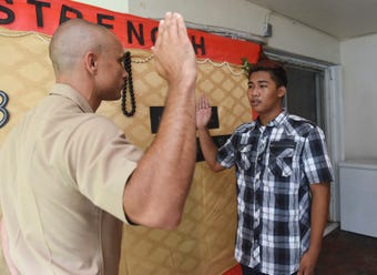 At the request of his terminally ill father, U.S. Marines recruit Keone Labra, 17, holds his enlistment ceremony at his home in Santa Rita, July 20, 2018.
