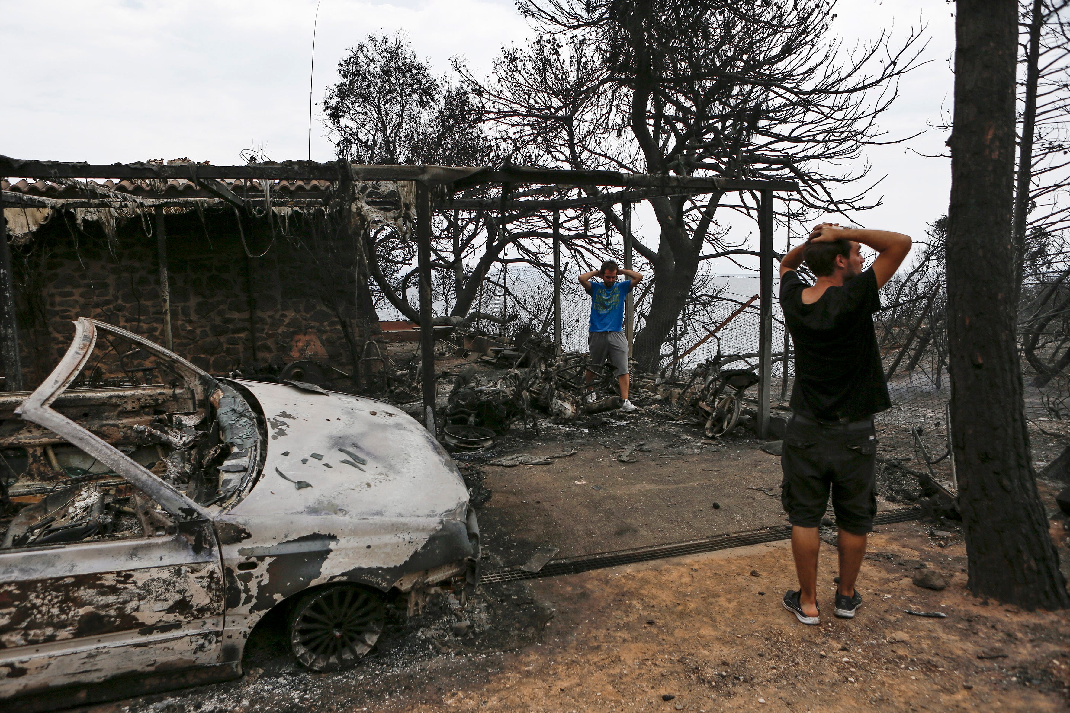 Residents react as they look at their burned house following a forest fire in Mati a northeast suburb of Athens, Greece. At least 50 people have lost their lives in wildfires that broke out in eastern Attica and there are fears of more casualties.