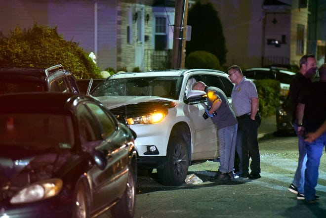 Crime Scene Investigators look inside a car that crashed into a parked car on East 34th Street in Paterson early Thursday morning.
