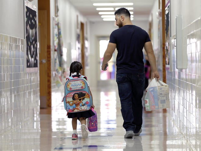 Adrian Rivera walks his daughter Abigail Rivera, 5, to her kinder classroom at Dr. Sue A. Shook Elementary in 2018 on the first day of school.