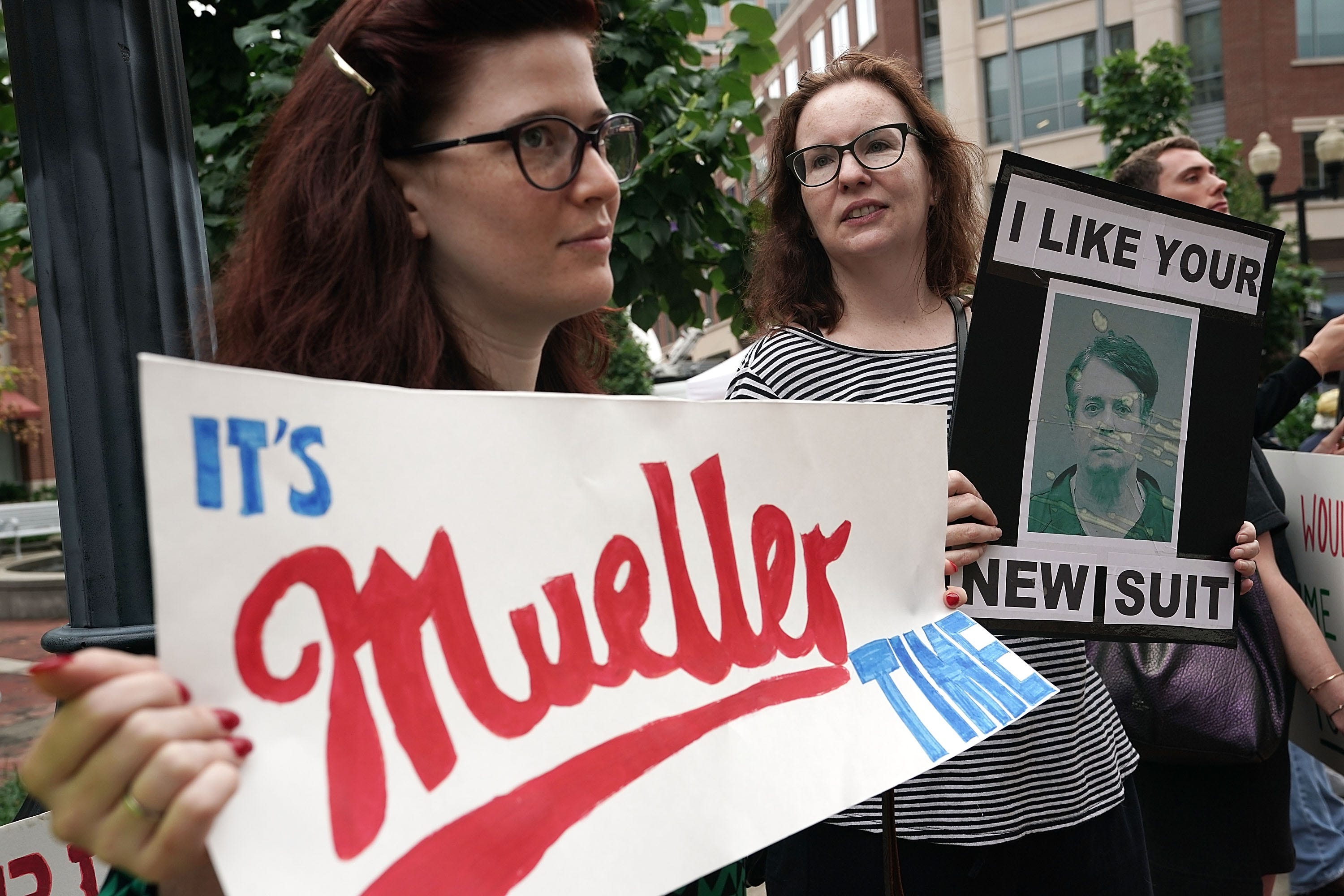 Activists hold signs during a protest outside the Albert V. Bryan United States Courthouse prior to the first day of the trial of former Trump campaign chairman Paul Manafort July 31, 2018 in Alexandria, Va. Manafort was charged with financial frauds