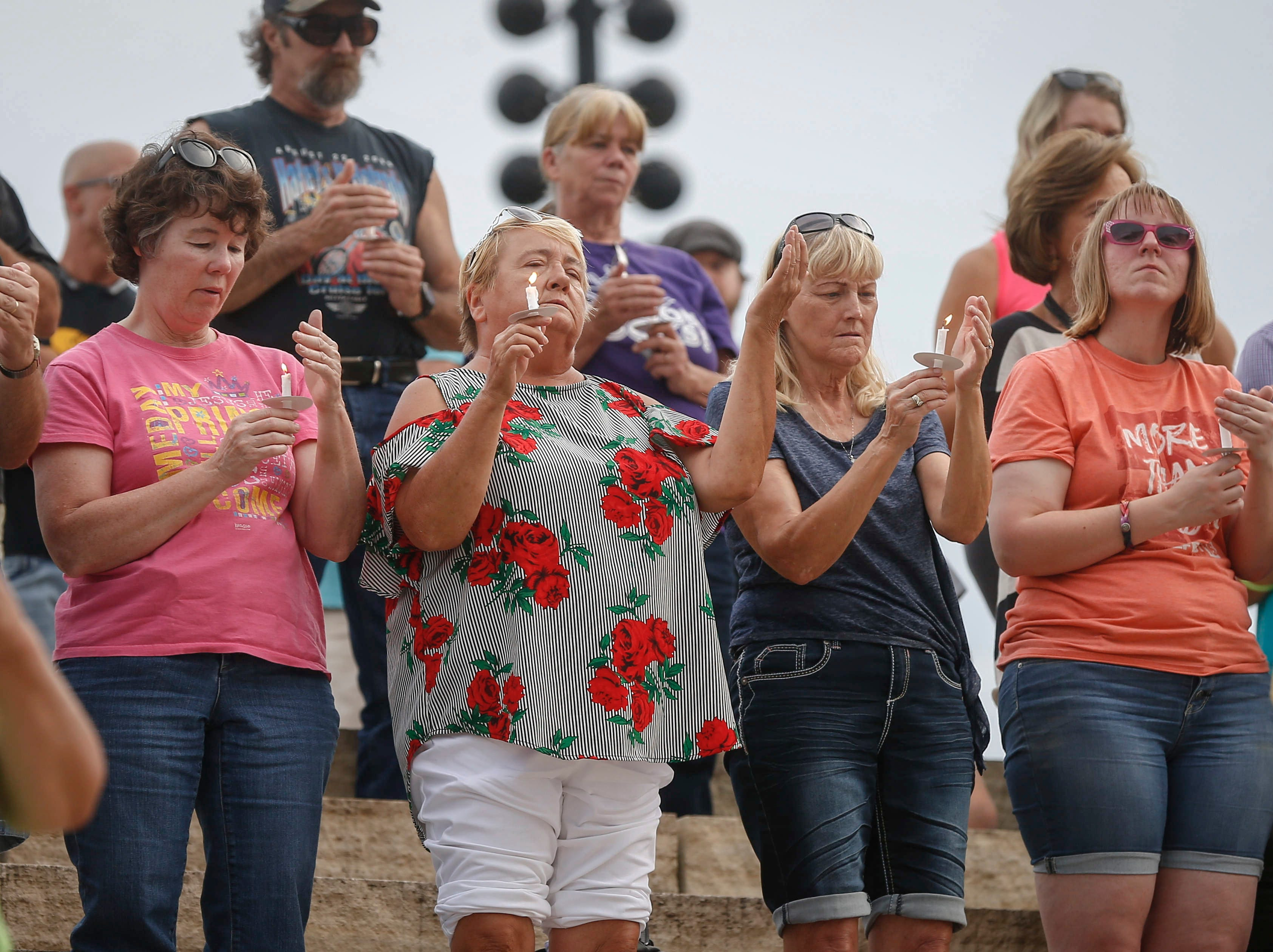 People raise lit candles during an August 2018 vigil for Iowa's missing children, including Mollie Tibbetts.