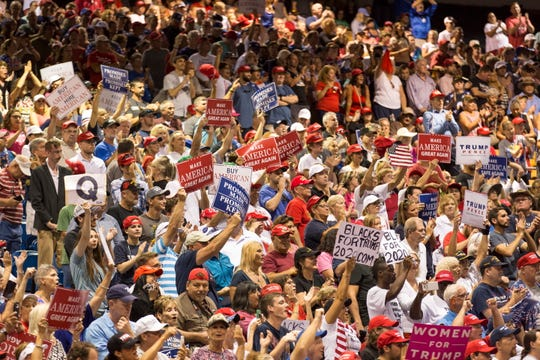 Among a crowd cheering as President Donald Trump speaks July 31 at the Florida State Fairgrounds Expo Hall in Tampa is a sign showing the letter Q, which could stand for QAnon, a conspiracy theory.