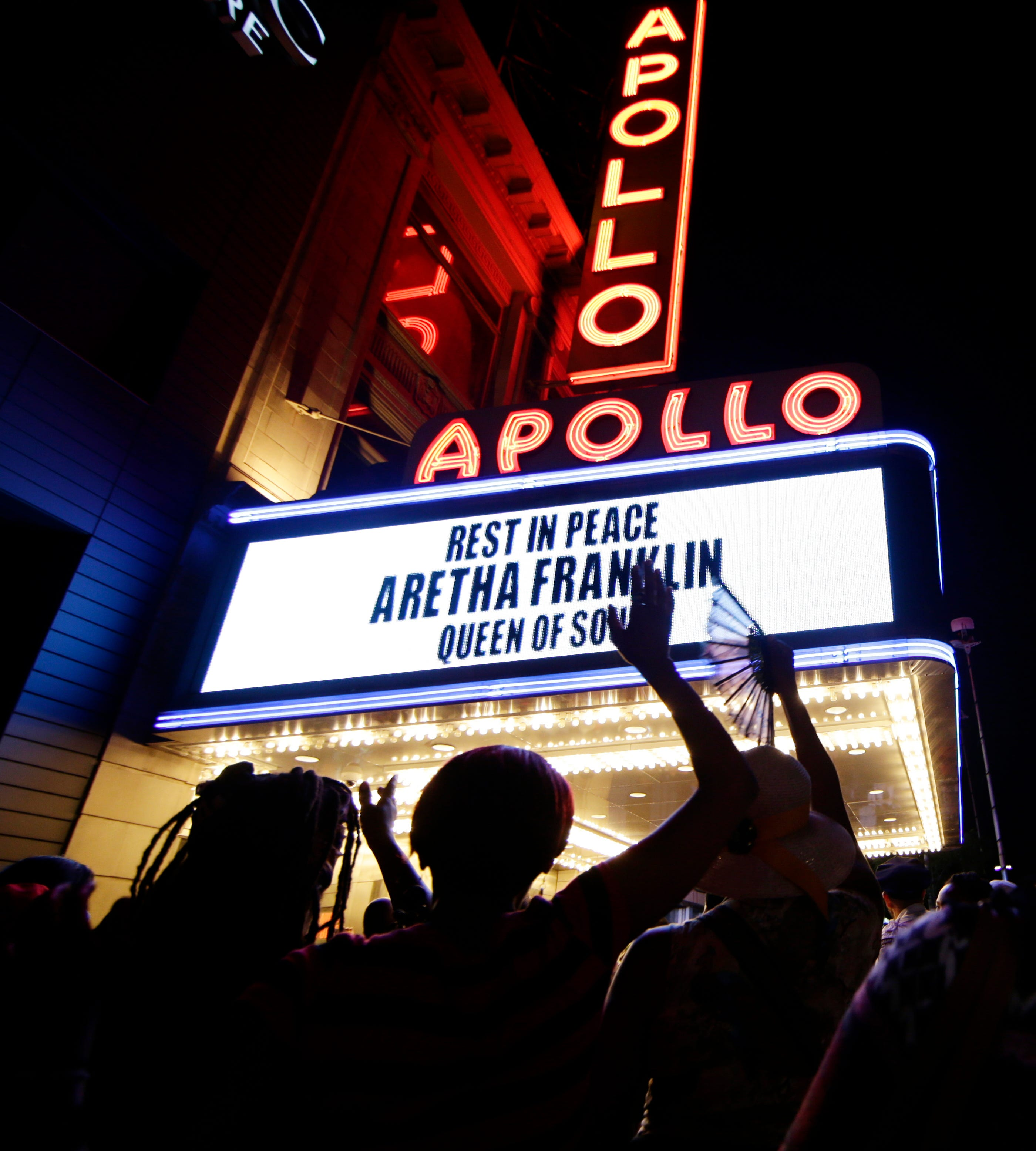 People gather at a makeshift memorial at the nameplate for singer Aretha Franklin outside the famed Apollo Theater in Aug. 16, 2018, in New York. Franklin died in her home in Detroit at age 76 from pancreatic cancer.
