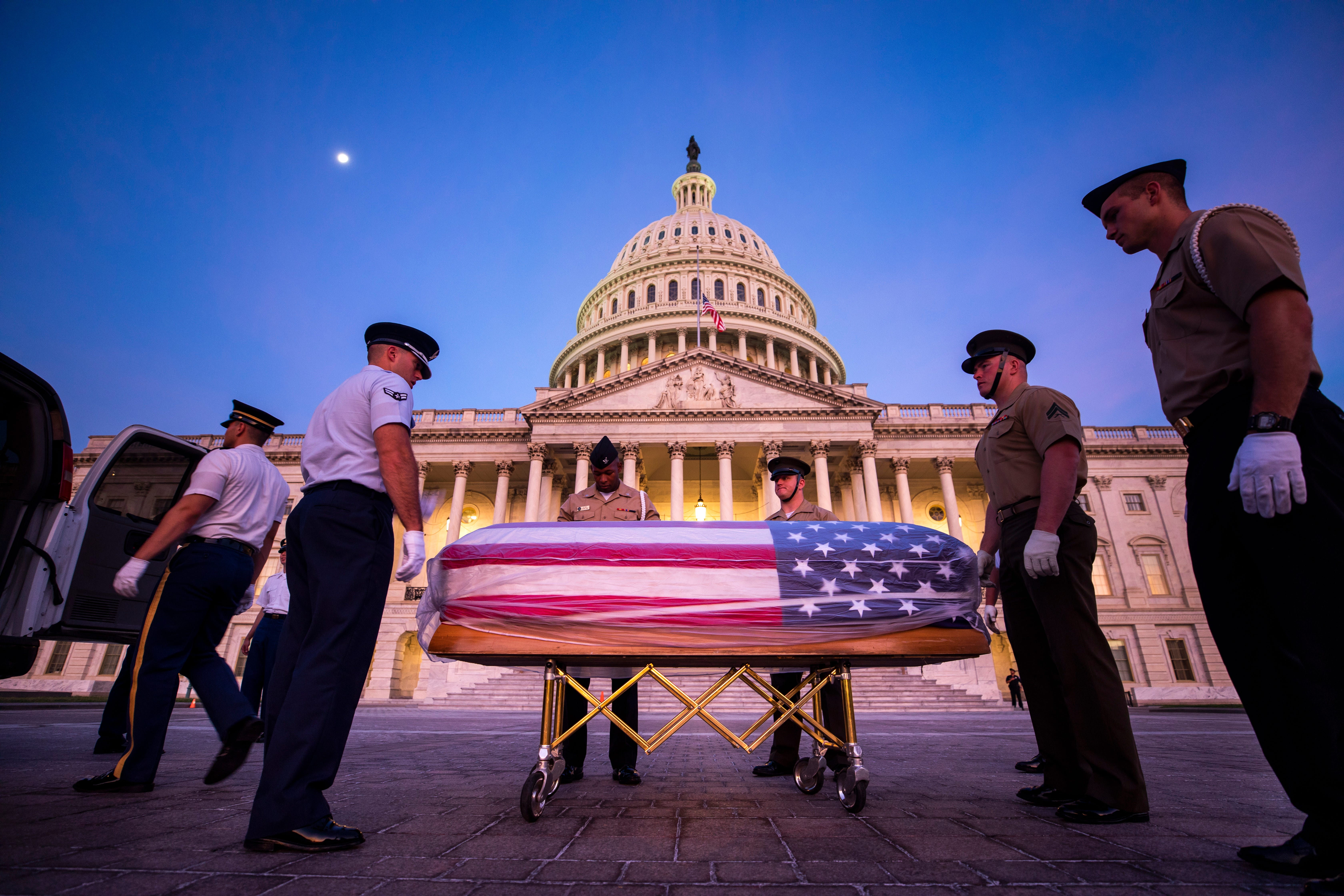 Joint service members of a military casket team use a stand-in for the casket of Senator John McCain to rehearse carrying the casket of into the US Capitol, where he will lie in state for one day in Washington, DC, Aug. 30, 2018. McCain died Aug. 25,