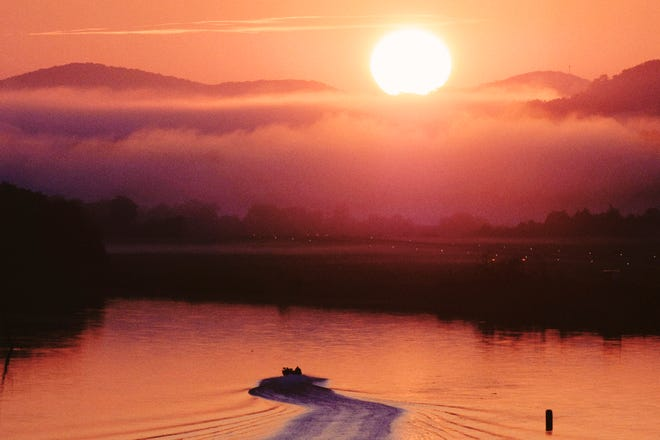 A fishing boat travels east down the Tennessee River as the sun rises above a foggy mountain range on Monday, September 3, 2018. The runway lights to Island Home Airport can be seen in the distance.