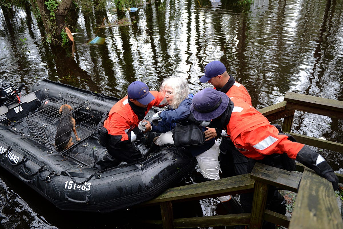 Members of Coast Guard rescue an elderly woman and her husband along with their pets in Brunswick County, N.C.