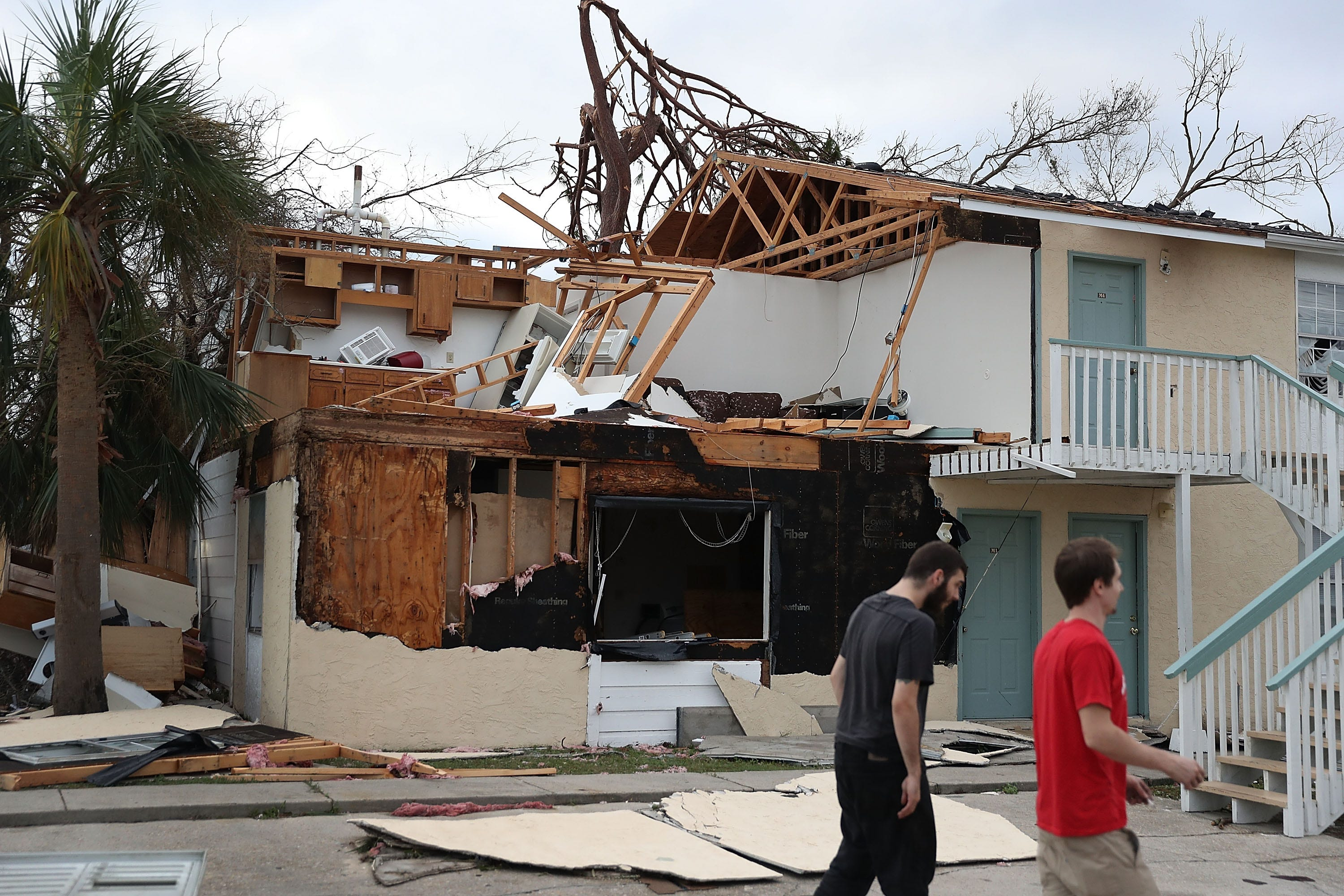 PANAMA CITY, FL - OCTOBER 11:  People walk past an apartment destroyed by Hurricane Michael on October 11, 2018 in Panama City, Florida. The hurricane hit the Florida Panhandle as a category 4 storm.  (Photo by Joe Raedle/Getty Images) ORG XMIT: 775241167 ORIG FILE ID: 1051884006