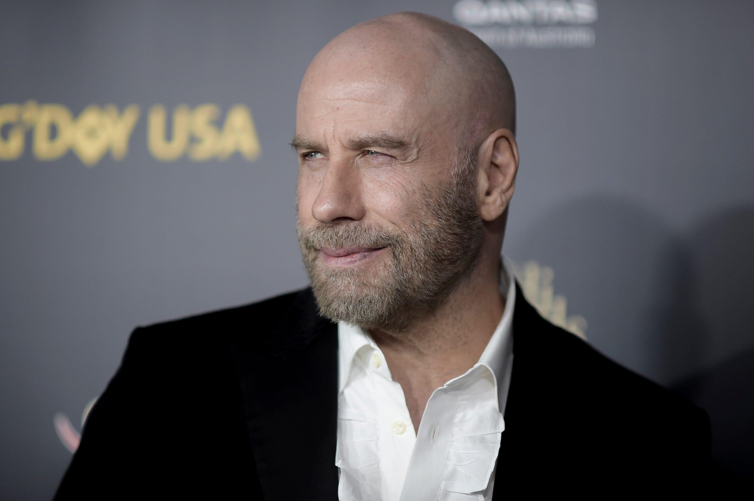 John Travolta says his bald look is his biggest news since Oscar flub, credits Pitbull