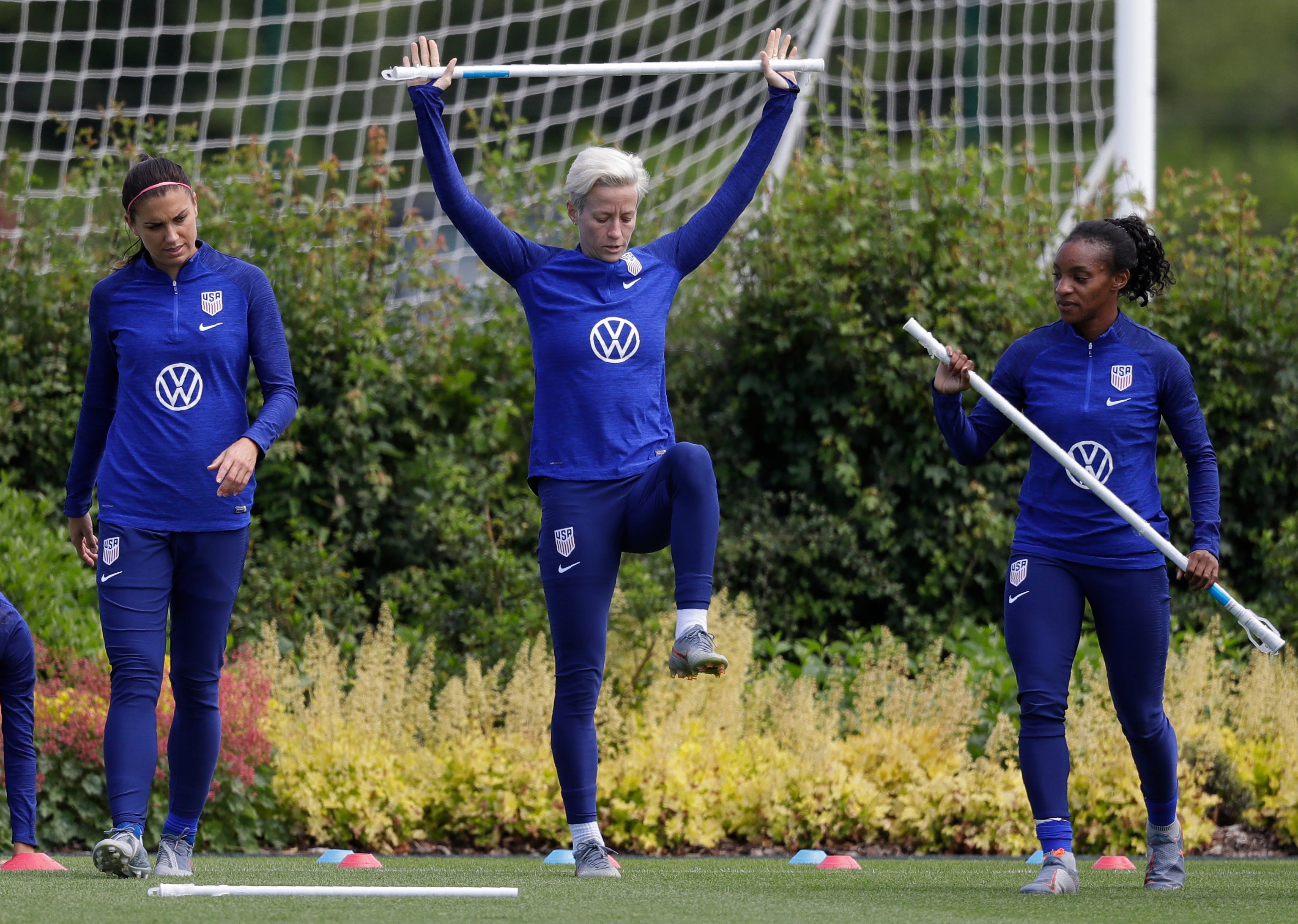 US player Megan Rapinoe, center, stretches with Crystal Dunn, right, and Alex Morgan, left, during a US womens soccer team training session at the Tottenham Hotspur training centre in London, Thursday, June 6, 2019. The Women's World Cup starts in France on June 7. (AP Photo/Kirsty Wigglesworth)