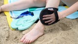 The Sand-Off Mitt removes sand from all over your body when you're at the beach this summer.