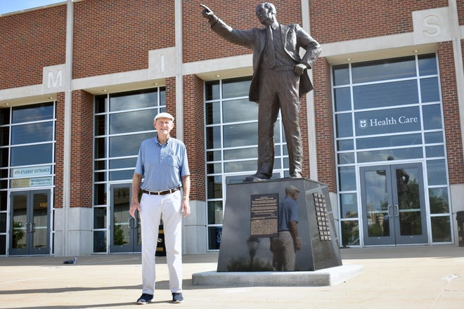 Former Missouri head men's basketball coach Norm Stewart poses next to a statue of him outside Mizzou Arena.
