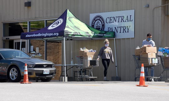 Workers bring food Wednesday to clients of the Central Food Pantry at 1007 Big Bear Blvd. Because of the COVID-19 pandemic, the pantry has changed to a drive-in operation. Food pantry hours are Tuesday through Saturday from 10 a.m. to 2 p.m.