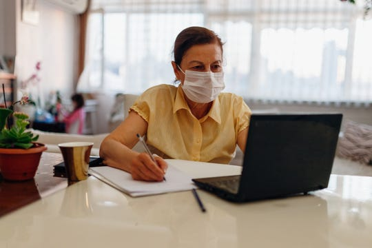 Woman working from home on her laptop wearing a mask.