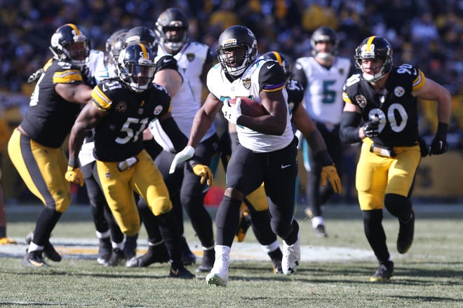 Jacksonville Jaguars running back Leonard Fournette (27) carries the ball past Pittsburgh Steelers linebacker Sean Spence (51) and outside linebacker T.J. Watt (90) in the AFC Divisional Playoff game at Heinz Field in 2018.