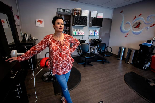Naomi Bartolacci stands at her station at Like Butterflies Salon on Tuesday in Avondale Estates, Ga. Bartolacci and her co-workers voluntarily closed the salon as the new coronavirus spread, but they are discussing how soon to open the doors to customers again in light of Georgia Gov. Brian Kemp's plan to allow businesses like salons to reopen this weekend.