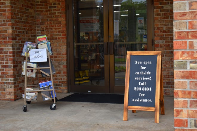 A cart of books and a sign announcing curbside service flank the doors at Champion Public Library Tuesday. Southern Oklahoma Library System branches are scheduled to resume limited services Wednesday while following health guidelines.