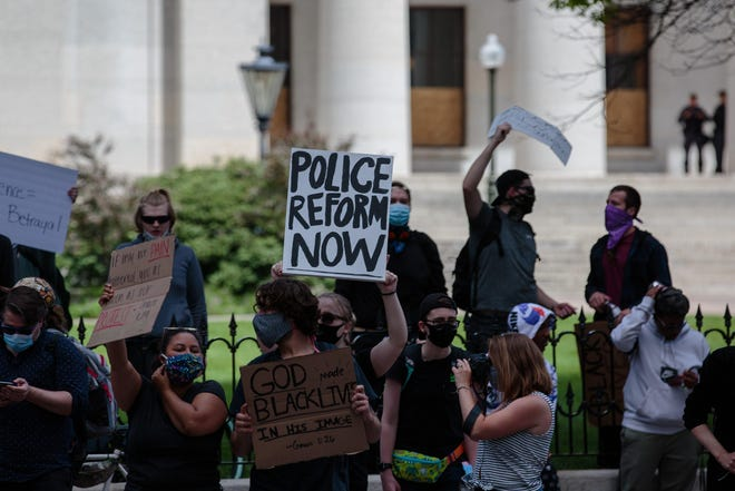 """A protester holds a sign that reads """"Police Reform Now"""" as protests continue following the death of Minneapolis resident George Floyd on Monday, June 1, 2020 in Columbus, Ohio."""