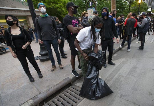 Joseph Kamara volunteers to clean up trash during a peaceful protest for George Floyd in downtown Columbus on Monday, June 1, 2020.