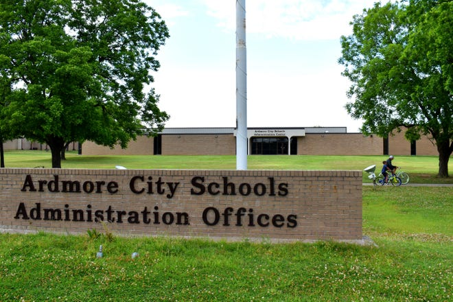 Cyclists ride past the Ardmore City Schools administration offices.