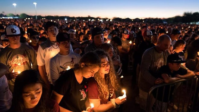 People attend a candlelit memorial service for the victims of the shooting at Marjory Stoneman Douglas High School that killed 17 people on Thursday, Feb. 15, 2018, in Parkland, Florida.