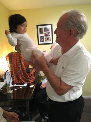 In pre-pandemic times, the Rev. Frank O'Loughlin, executive director of the Guatemalan-Maya Center, holds up one of the center's youngest clients.