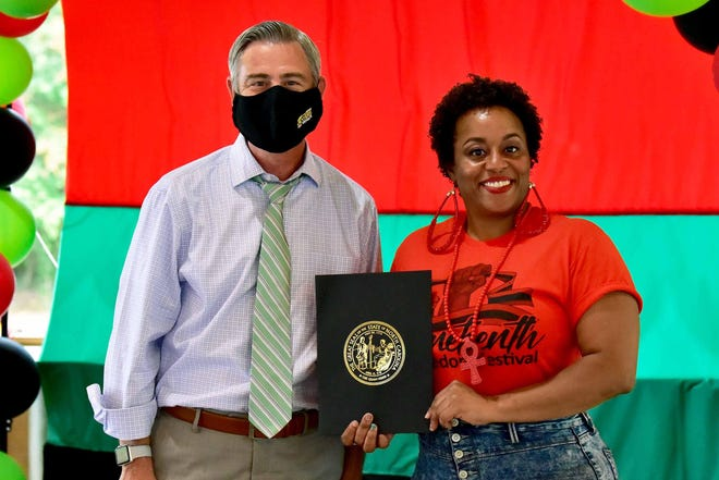 Juneteenth Freedom Festival organizer Kia Anthony stands with N.C. State Sen. Kirk Deviere after receiving a Juneteeth proclamation on June 19, 2020.