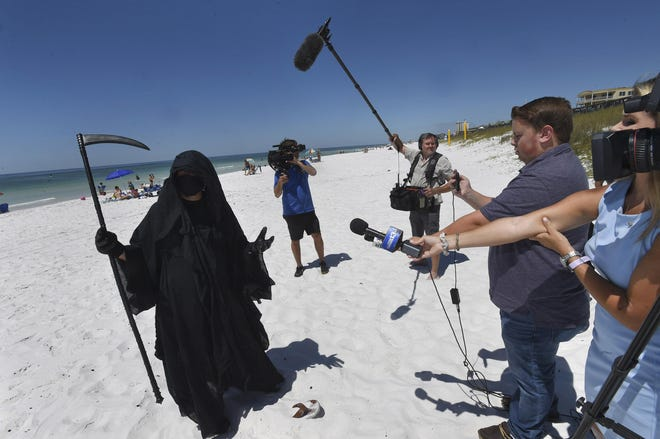 Dressed as the Grim Reaper, Walton County attorney Daniel Uhlfelder talks with reporters after walking the newly opened beach in Miramar Beach earlier this year  to protest the Walton County Commissions decision to reopen the beaches in spite of the COVID-19 pandemic.