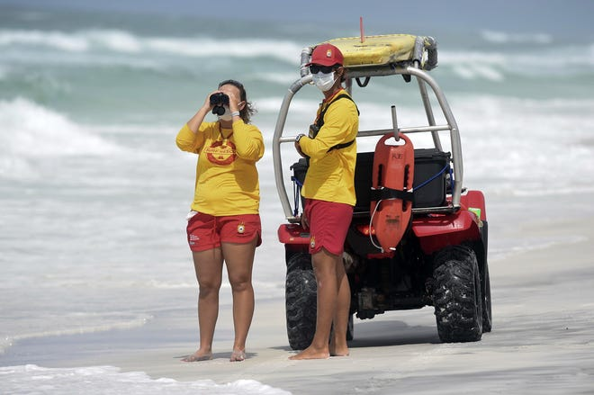 South Walton Beach Safety Lifeguards MaKena Kimball and Ian Rogers spot a swimmer in the water under double-red flag conditions at Ed Walline Park earlier this year.