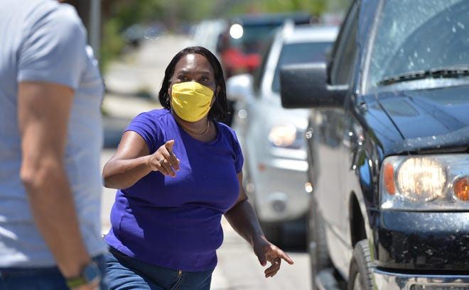 April Glasco, founder of Second Chance-Last Opportunity, directs traffic and volunteers on Wednesday at Dr. Martin Luther King Way and Dixie Ave. in Sarasota, during a food giveaway.