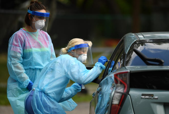 Nurses Katelyn Escanillas, left, and Beth Banko, right, collect samples in mid-May at Bethlehem Baptist Church in Sarasota, a temporary drive-thru testing site for COVID-19.