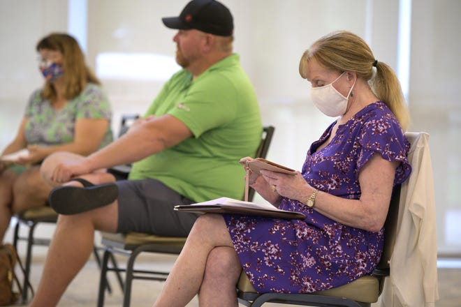 A woman wears a mask while attending a Leesburg commission meeting.