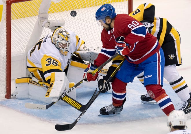 Pittsburgh Penguins goaltender Tristan Jarry (35) makes a save on Montreal Canadiens right wing Alex Belzile (60) as Penguins defenseman John Marino (6) helps out during the first period of an NHL hockey playoff game Friday, Aug. 7, 2020, in Toronto. (Frank Gunn/The Canadian Press via AP)