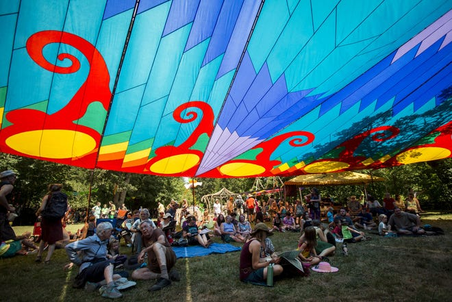 Fair attendees seek shade under a rainbow canopy on the first day of the 50th annual Oregon Country Fair on July 12, 2019.