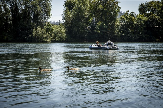 Two people float down the Willamette River on a 100-degree day in mid-August. Temperatures are predicted to stay in the 90s the rest of the week.
