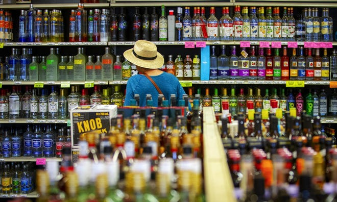 A customer at a Eugene liquor store peruses the vodka selections.