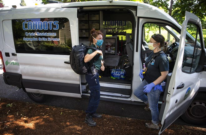 CAHOOTS emergency medical technician Summer Johnson, left, and crisis worker Amy May stop by Monroe Park in Eugene at the end of their 12-hour shift. The Eugene-based mobile crisis intervention program of White Bird Clinic has become a nationwide model as cities search for ways to handle calls for service without involving the police.