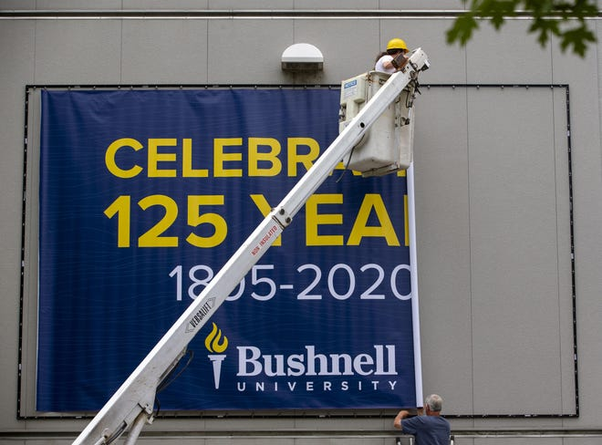 Fast Signs workers Will Hooker, top, and Dennis Hyde unfurl a banner noting the change of name at the Eugene educational institution from Northwest Christian University to Bushnell University.