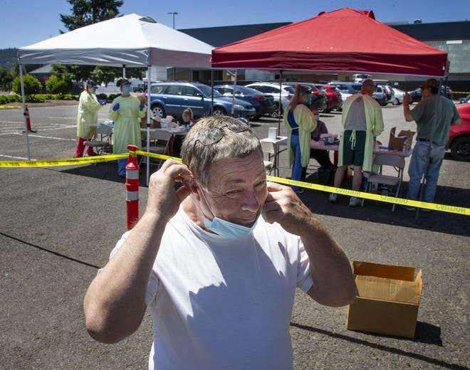With his eyes still watering, Kye Robson puts his mask back over his face after receiving a COVID-19 test during an outdoor testing opportunity for front-line workers at the Lane County Fairgrounds in Eugene.