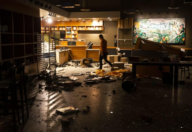 A man walk through the looted Starbucks in the early morning hours of May 30 after a May 29 protest in Eugene over the killing of George Floyd in Minneapolis, Minnesota.