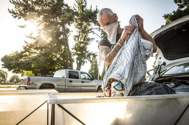 """Edward """"Ed"""" Ulbricht, 61, dumps cans and bottles into one of the Springfield BottleDrop carts. Oregon's can and bottle redemption program has seen a significant increase in participation since the pandemic started."""