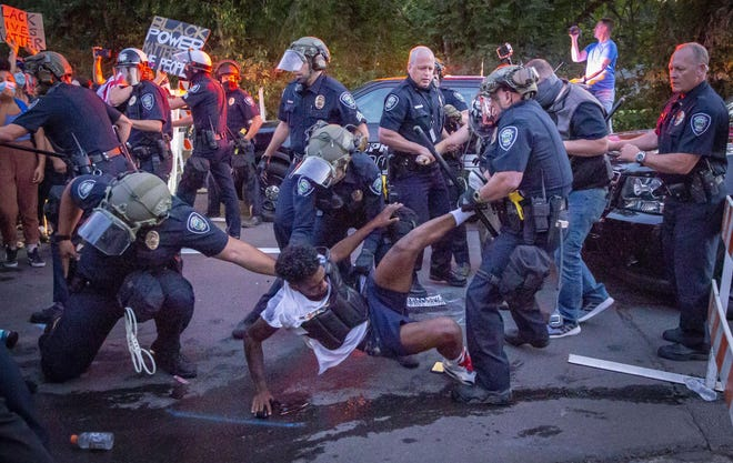 Black Unity's Tyshawn Ford is dragged away by Springfield Police July 29, 2020 at a barricade erected at 67th and Dogwood streets in Springfield, Oregon by police during the Thurston protest.