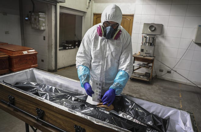 An employee takes the fingerprints of a woman who died from the new coronavirus before her remains are cremated at La Recoleta crematorium in Santiago, Chile, on Saturday. The Ministry of Health reported on Saturday the highest number of deaths in Chile since the start of the pandemic.