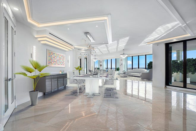In the foreground, the dining area of Penthouse 605 S at the Palm Beach Hampton is depicted in a digitally illustrated photo. The renovated condo is listed at $6.95 million.