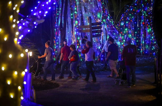 People enjoy the first night of Zoo Lights at the Palm Beach Zoo Friday, November 29, 2019 in West Palm Beach. The Palm Beach Zoo will be illuminated for the holidays with over one million eco-friendly lights. Each evening from 6 - 10pm the Zoo will be aglow with themed displays from the entrance through the Florida Wetlands and Tropics of the Americas. Visitors can also enjoy photos with Santa, special animal encounters, and Mrs. Claus' Kitchen featuring cookie decorating.