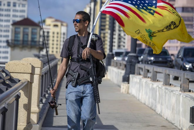 Michael Taylor walks along the Royal Park Bridge Friday armed with a Smith & Wesson MP 15-22 assault rifle and a Glock 23, along with a fishing pole.